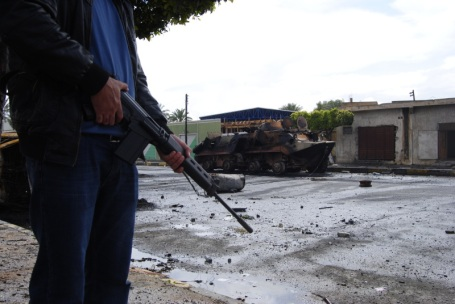 photo : sur une rue de la ville, un homme en vêtement civil, gillet de cordon bleu, et une AK47 dans les mais et immobile. Un blindé gît brûlé un peu plus loin.